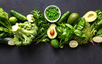 Raw healthy food clean eating vegetables: cucumber, alfalfa, zucchini, spinach, basil, green peas, dill, parsley, avocado, broccoli, lime on dark stone background, top view